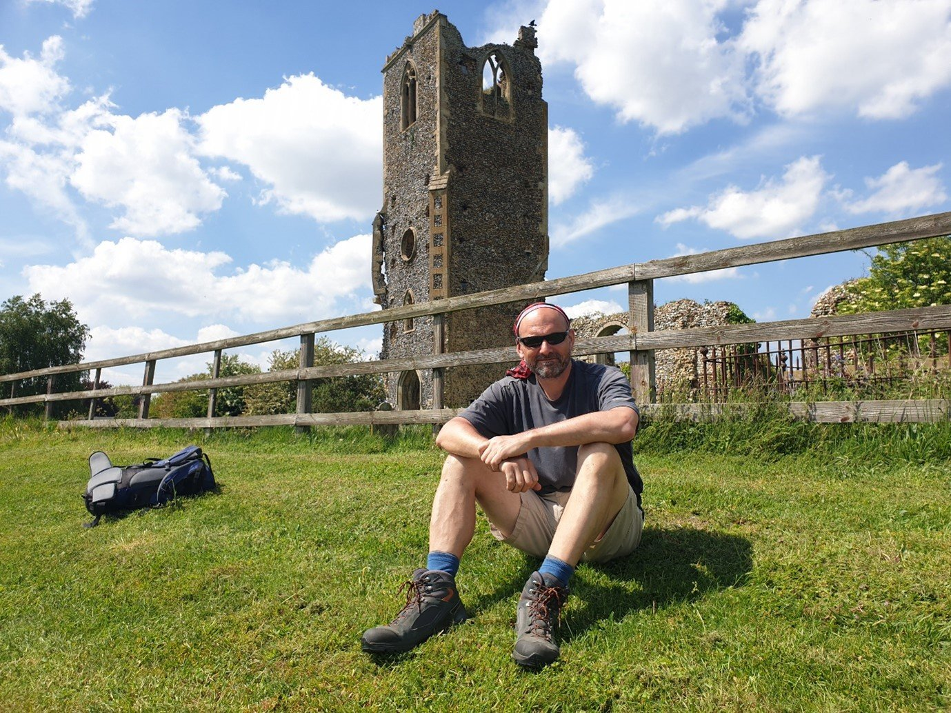 walking sitting with small ruck sack in green field in front ancient ruin showing how to travel light travel fast on uk walking holiday