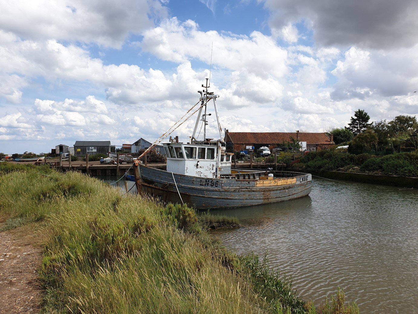 an image of a fishing boat in Norfolk salt marshes on the Norfolk coast path